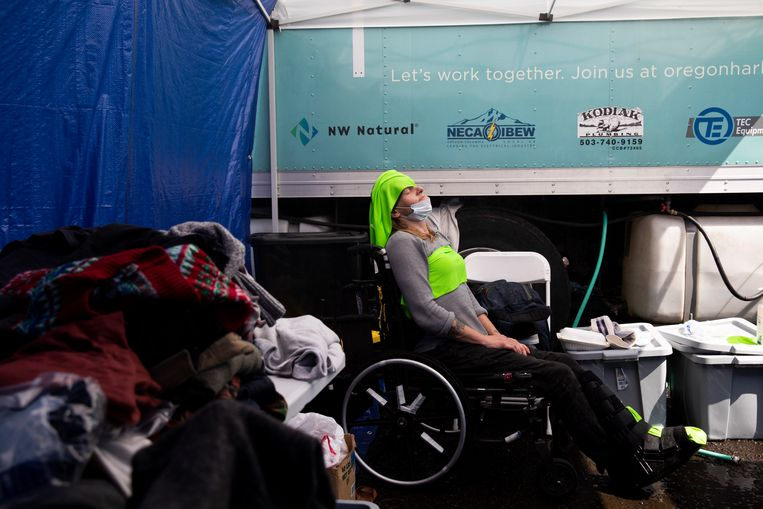 A woman in a cooling center wears cold clothes on her head and chest.  Washington Post image