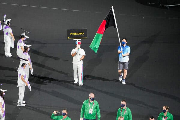A volunteer carrying the flag of Afghanistan in the place of the absent athletes,