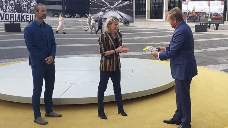 Koning Willem-Alexander krijgt een boek overhandigd door Ahoy-directeur Jolanda Jansen. Links presentator Jan Kooijman