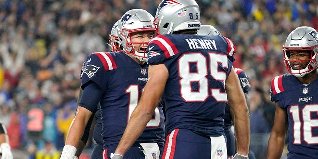 New England Patriots quarterback Mac Jones, left, celebrates after his touchdown pass to the tight end Hunter Henry (85) during the first half of an NFL football game against the Tampa Bay Buccaneers, Sunday, October 3, 2021, In Foxboro, Massachusetts.