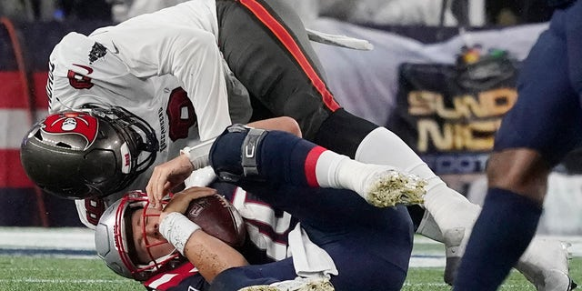 New England Patriots quarterback Mac Jones, lower back, is sacked by Tampa Bay Buccaneers quarterback Joe Tryon Soyinka (9) during the second half of an NFL football game, Sunday, October 3, 2021, in Foxboro, Massachusetts.