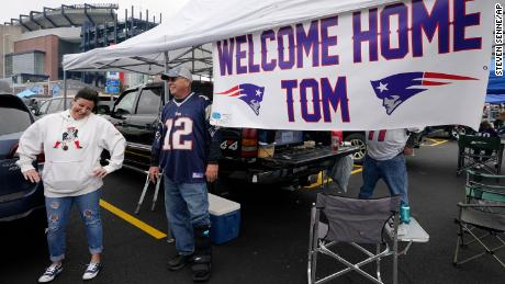 New England Patriots fans swing by a banner saluting Brady's return.